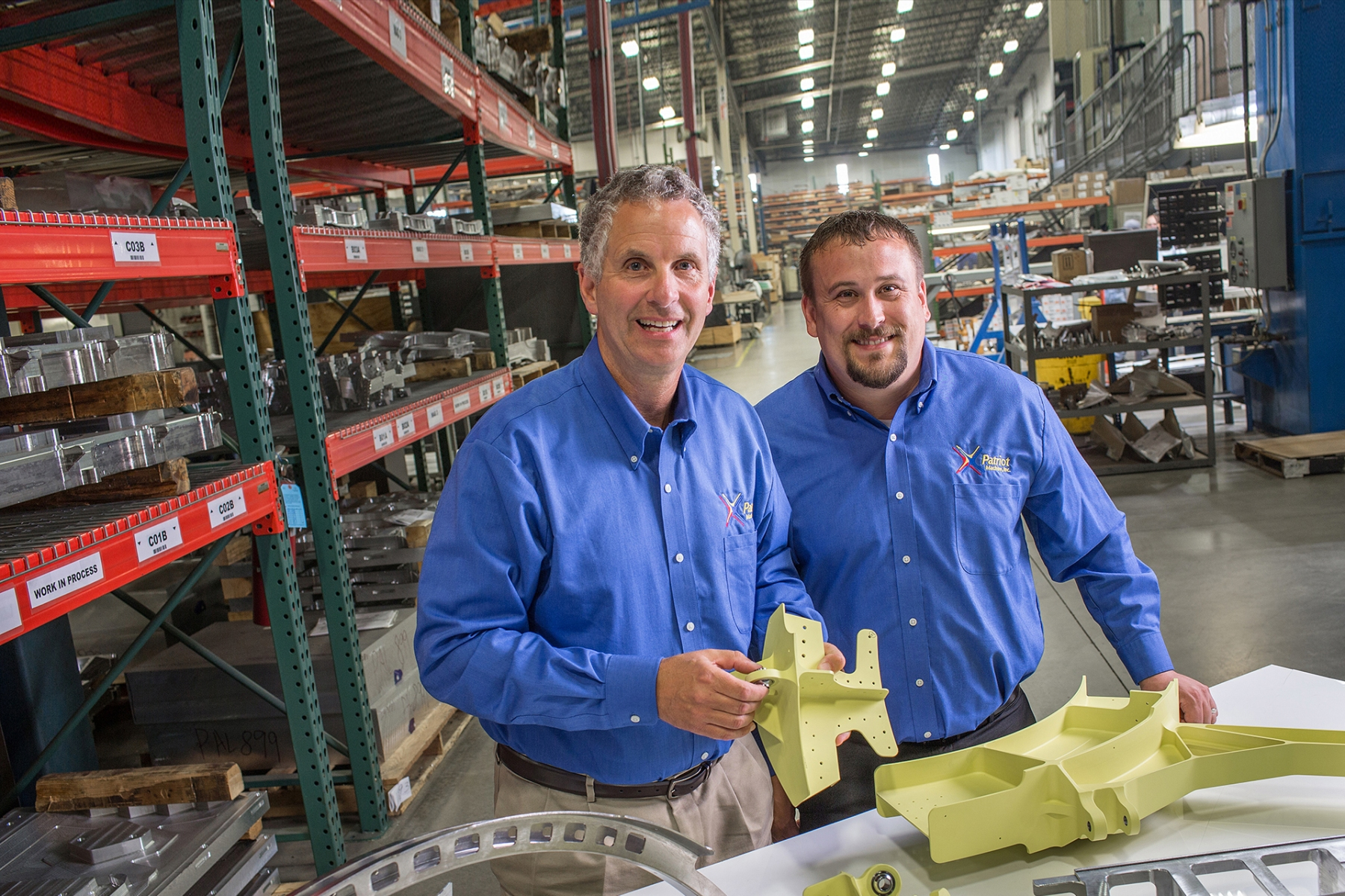 Two Patriot Machine associates on the shop floor, with some machined parts on a table in front.