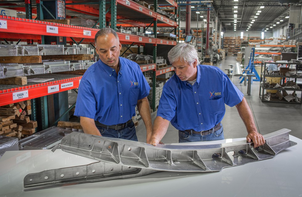 Two Patriot Machine associates examining a part on a table together.