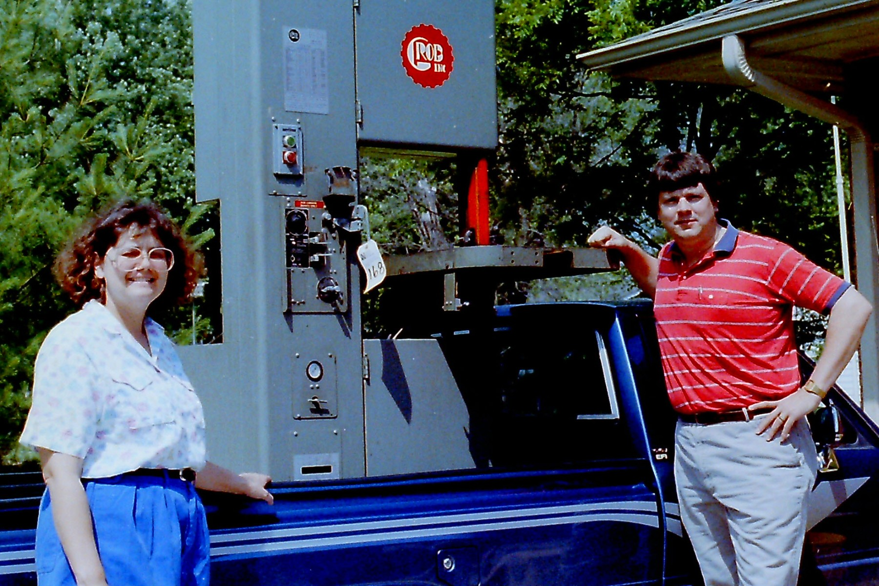 Young Bob and Judy Burns standing in front of a truck, their first machine in the bed.